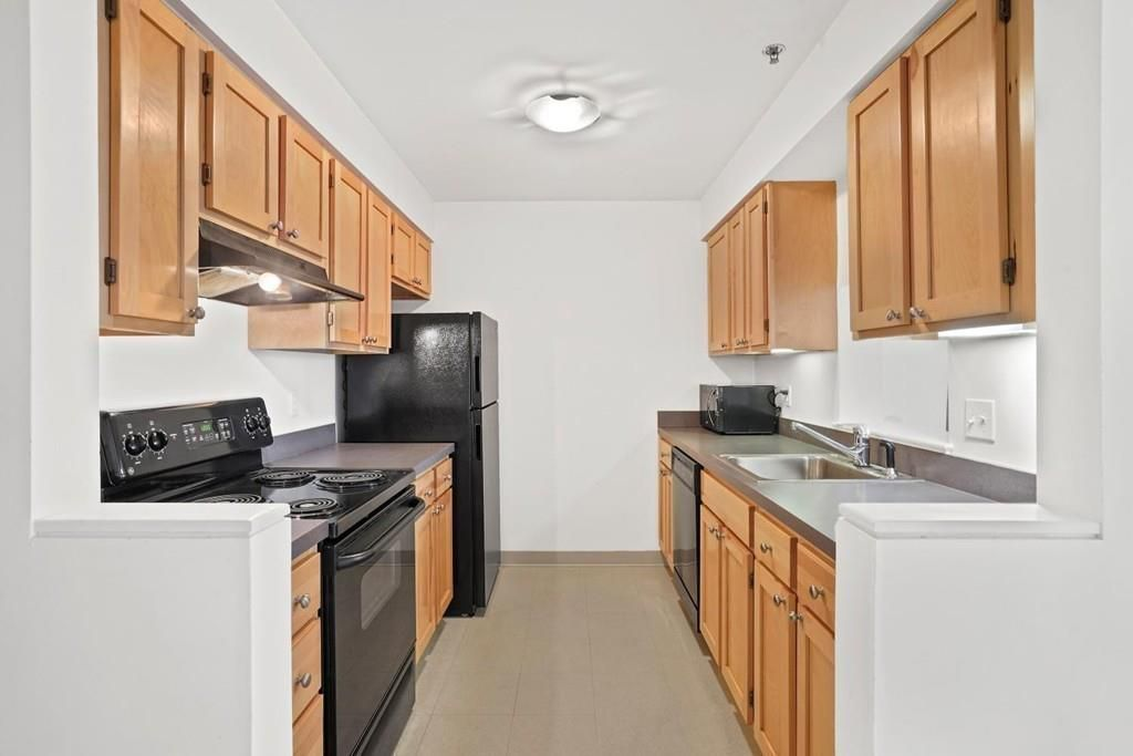 A long kitchen with counters and cabinetry (and appliances) on either side of a passageway.