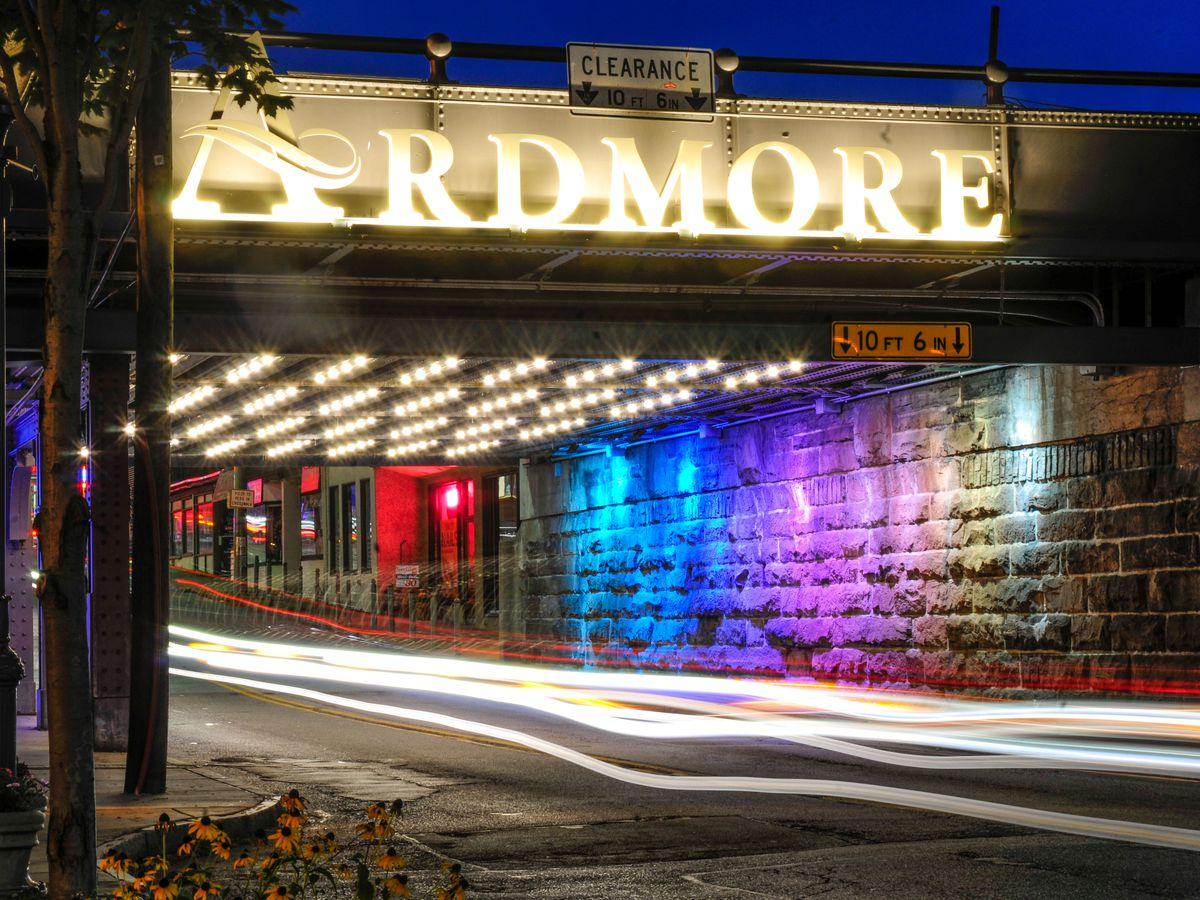 A street with the lights of a car in motion. Over the street is a sign that reads: Ardmore.