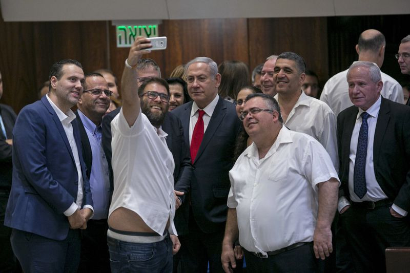 Knesset member Oren Hazan takes a selfie with Israel's Prime Minister Benjamin Netanyahu, center, and MP David Bitan, right of Netanyahu, to celebrate the passing of the nation-state bill on July 19, 2018, in Jerusalem.