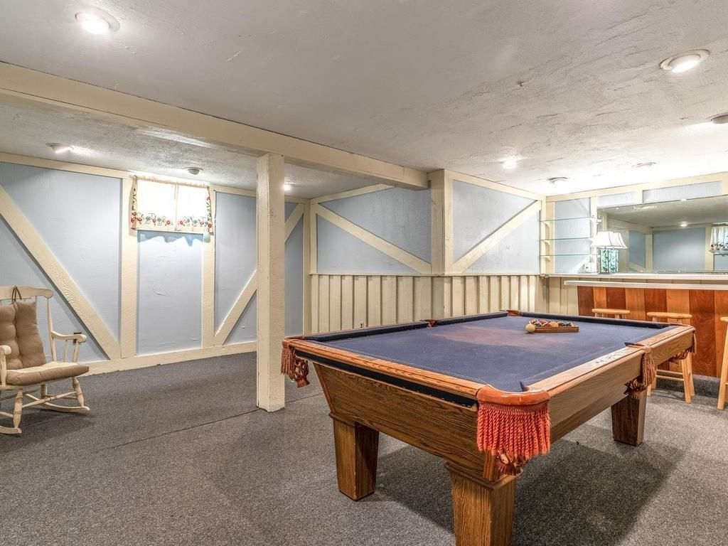 A room with a pool table, and there's a column in the room.