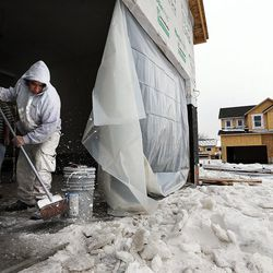 Before doing sheetrock work, Rodrigues Zion clears snow from the garage floor of a home being built in Farmington on Thursday, Feb. 4, 2016.