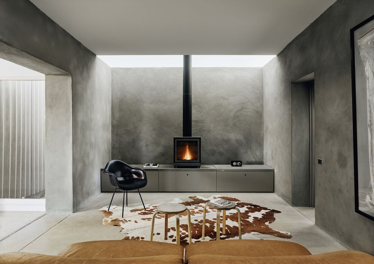 A black wood stove is centerstage in the living room. It has a modern Eames chair and two low stools in front of it.