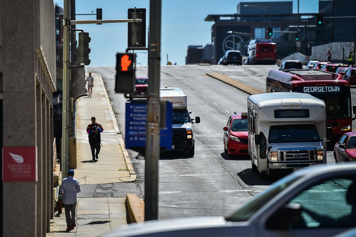 A three-lane road in a city. Cars, buses, and vans are pointed toward the camera. A crossing sign is shown with a red hand.