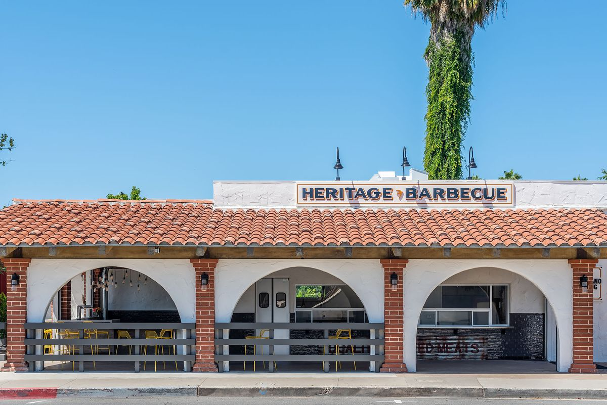 The exterior of Heritage Barbecue complete with open-air windows and outdoor seating.