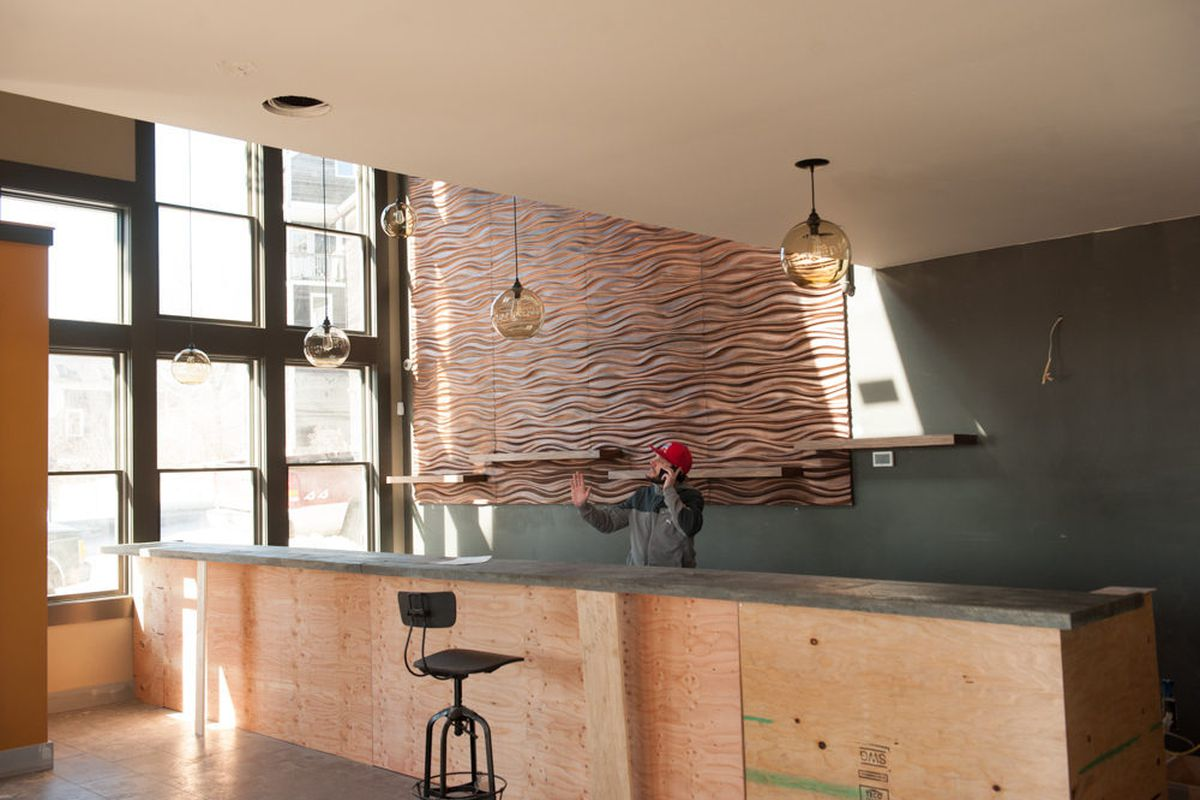 Outliers owner Peter Verrill behind the bar. In the foreground is a sample of the barstools.