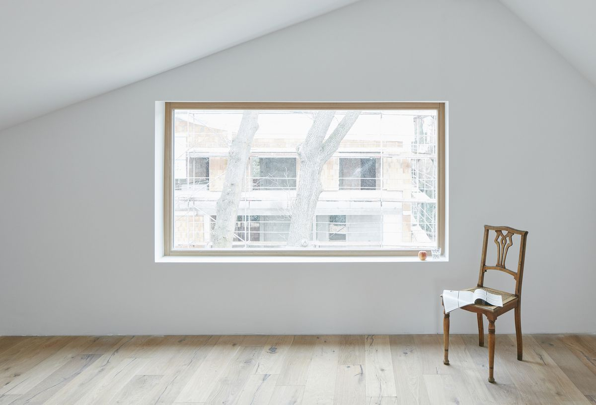 Room with angled ceiling and long horizontal window.