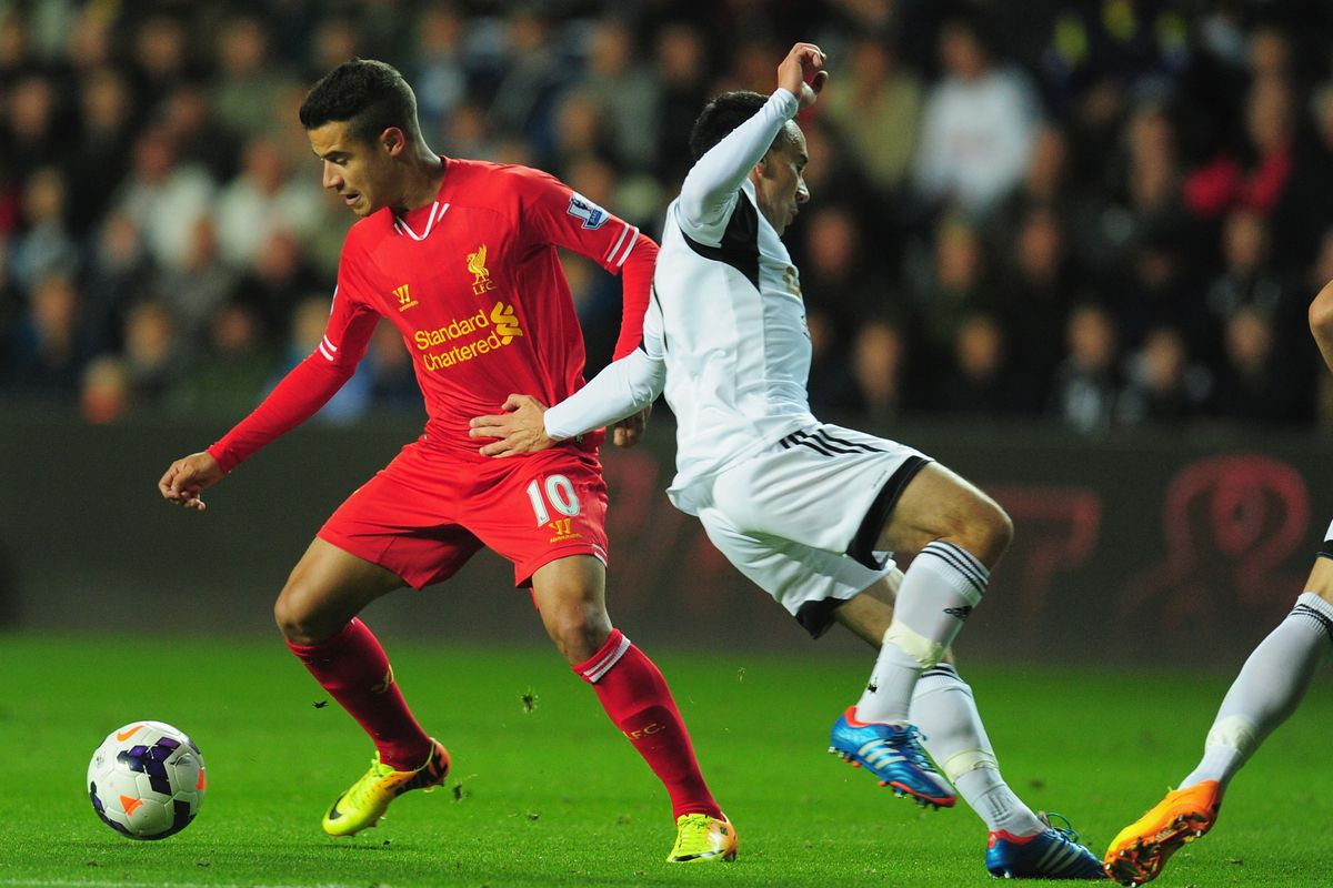 Philippe Coutinho upright, despite Swansea's best efforts.