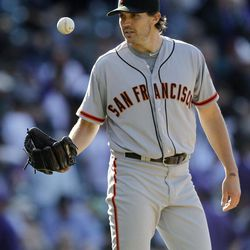 San Francisco Giants starting pitcher Barry Zito catches the game ball after his complete-game shutout of the Colorado Rockies in the Giants' 7-0 victory in a baseball game in Denver on Monday, April 9, 2012.