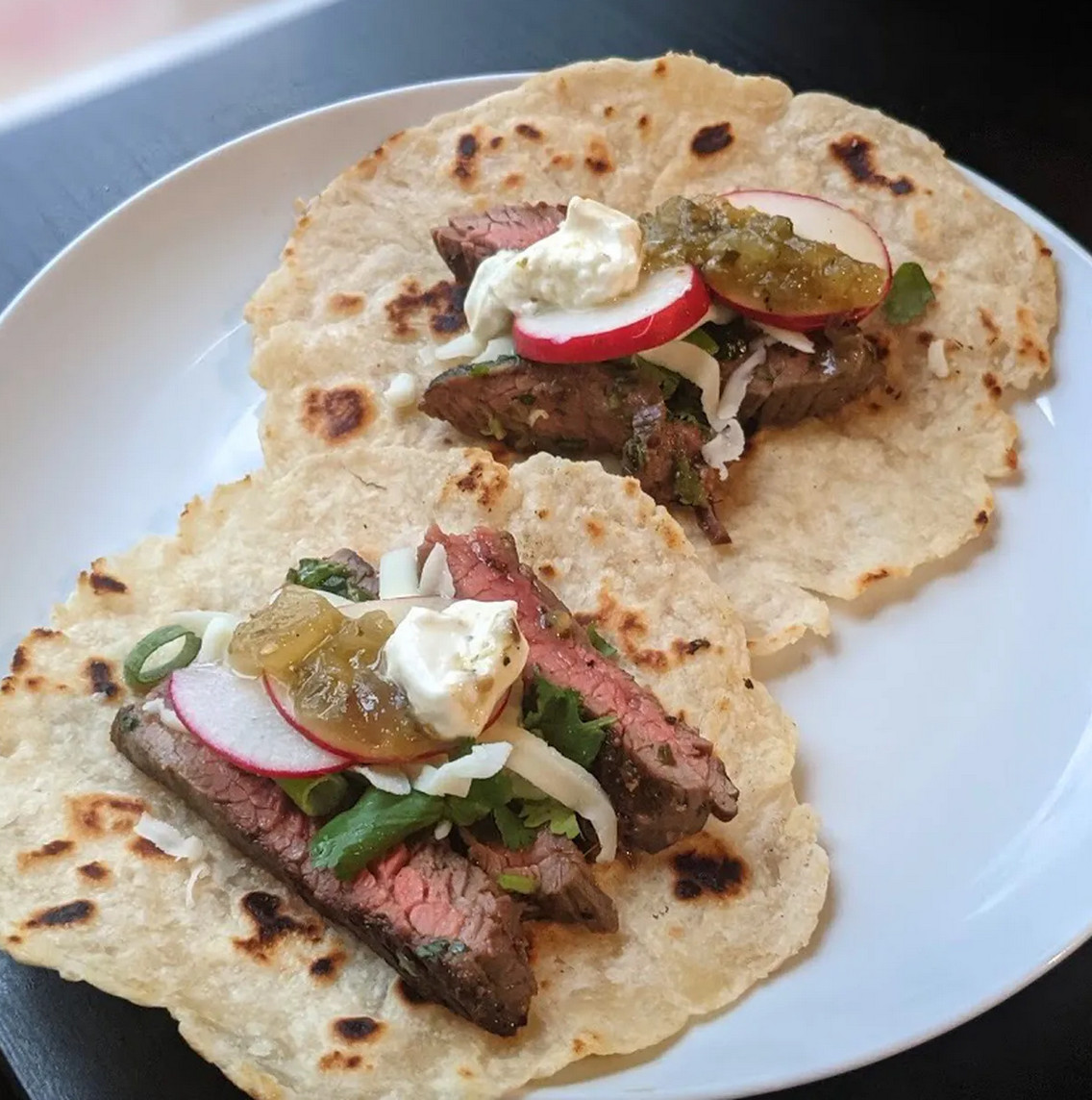 Two steak tacos with flour tortillas, sitting on a white plate.