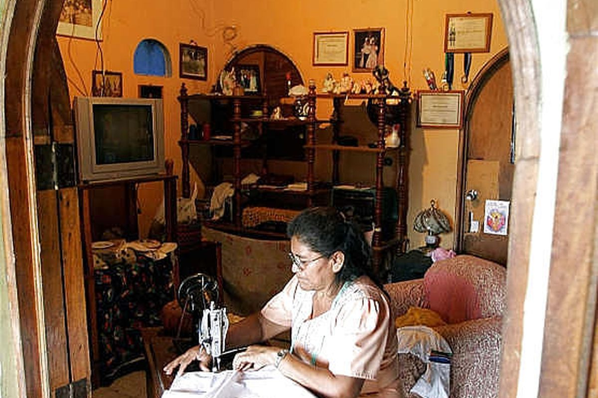 Nolberta Melara sews an apron at her house in the Salvadorean city of San Marcos on Oct. 13, 2006. To support her family financially, Melara makes aprones and then sells them in markets across the country. The 51-year-old woman saw her life transformed th