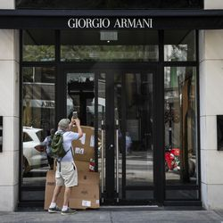 A man takes a photo of the Giorgio Armani store at 25 E. Oak St. after looting broke out overnight in the Gold Coast and surrounding neighborhoods, Monday morning, Aug. 10, 2020.