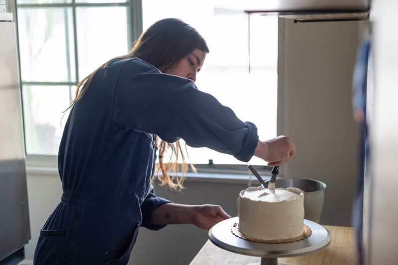 Woman wearing jumpsuit applies white icing to the outside of a cake sitting on a cake stand.