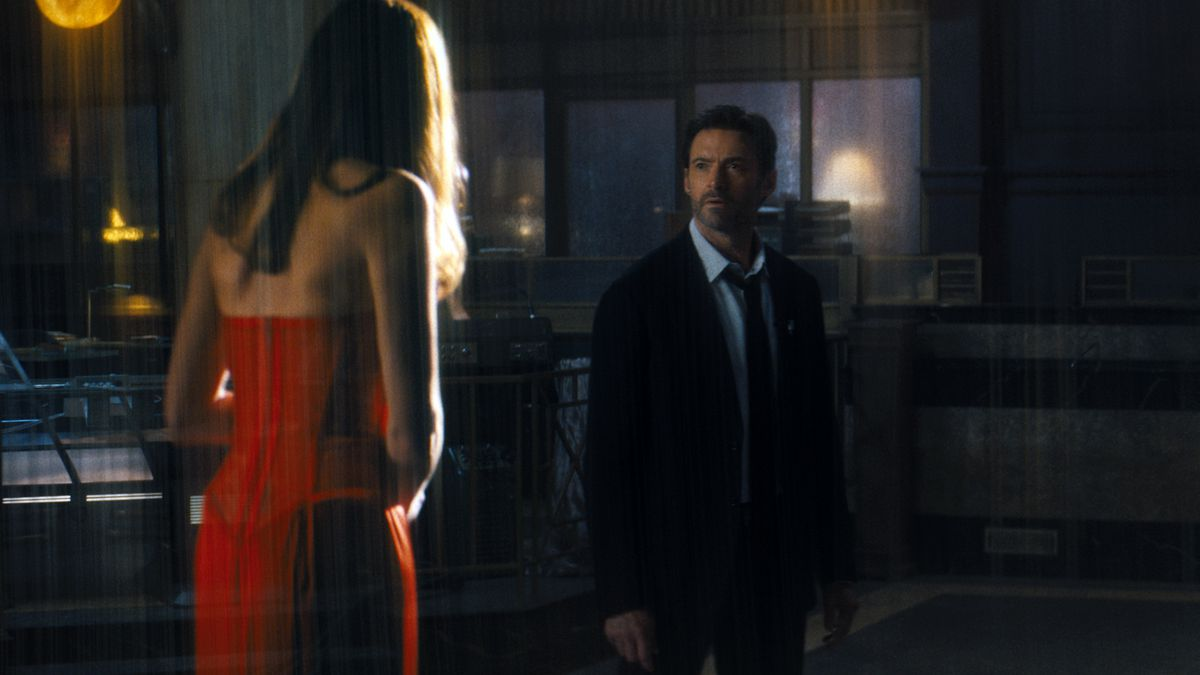 Nick Bannister (Hugh Jackman) looks at a holographic woman in a red dress in Reminiscence