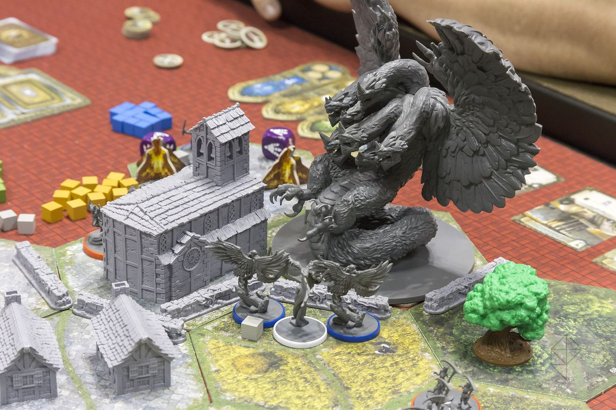 A multi-headed dragon battles against a flight of angels in the shadow of rustic church in the Joan of Arc line of miniatures.