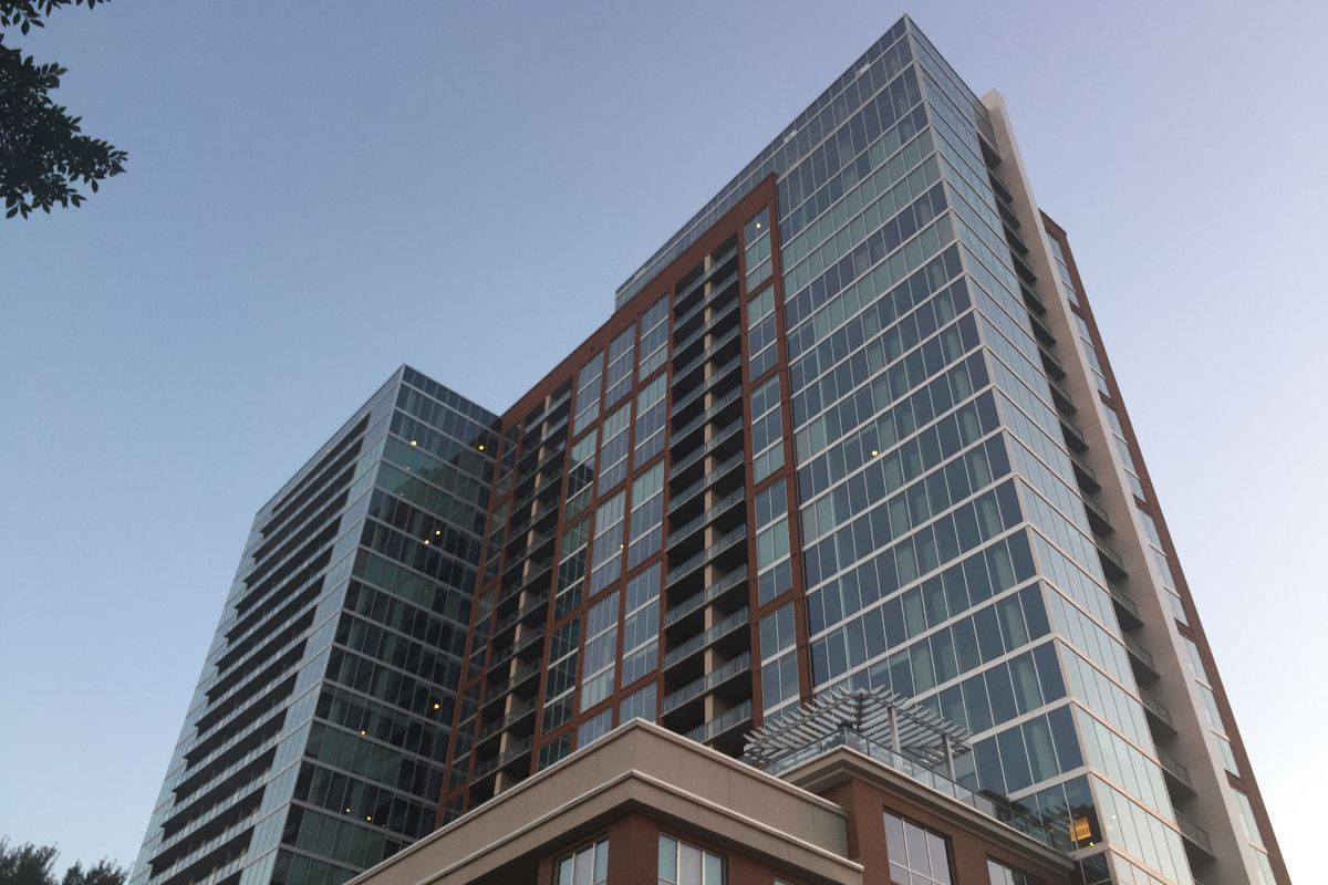 A glass tower atop a red brick base.