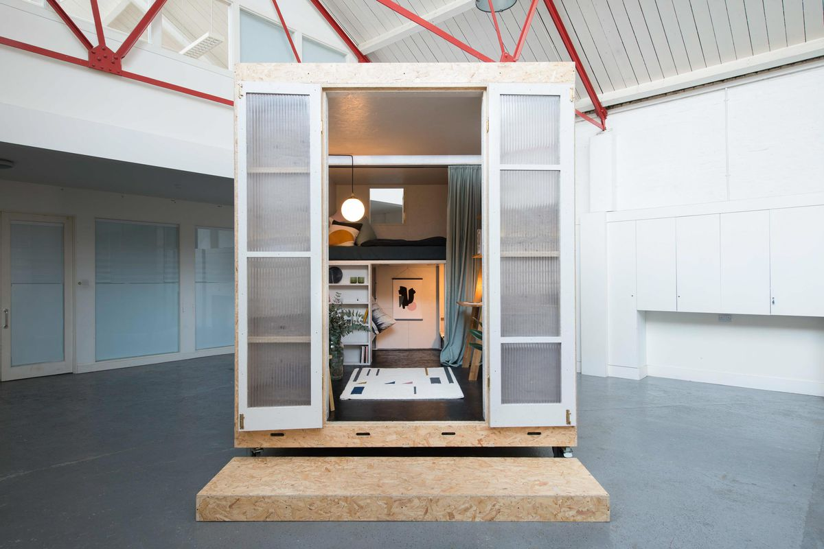Photo of a small box home made with particle board and plastic doors set in a vacant building.