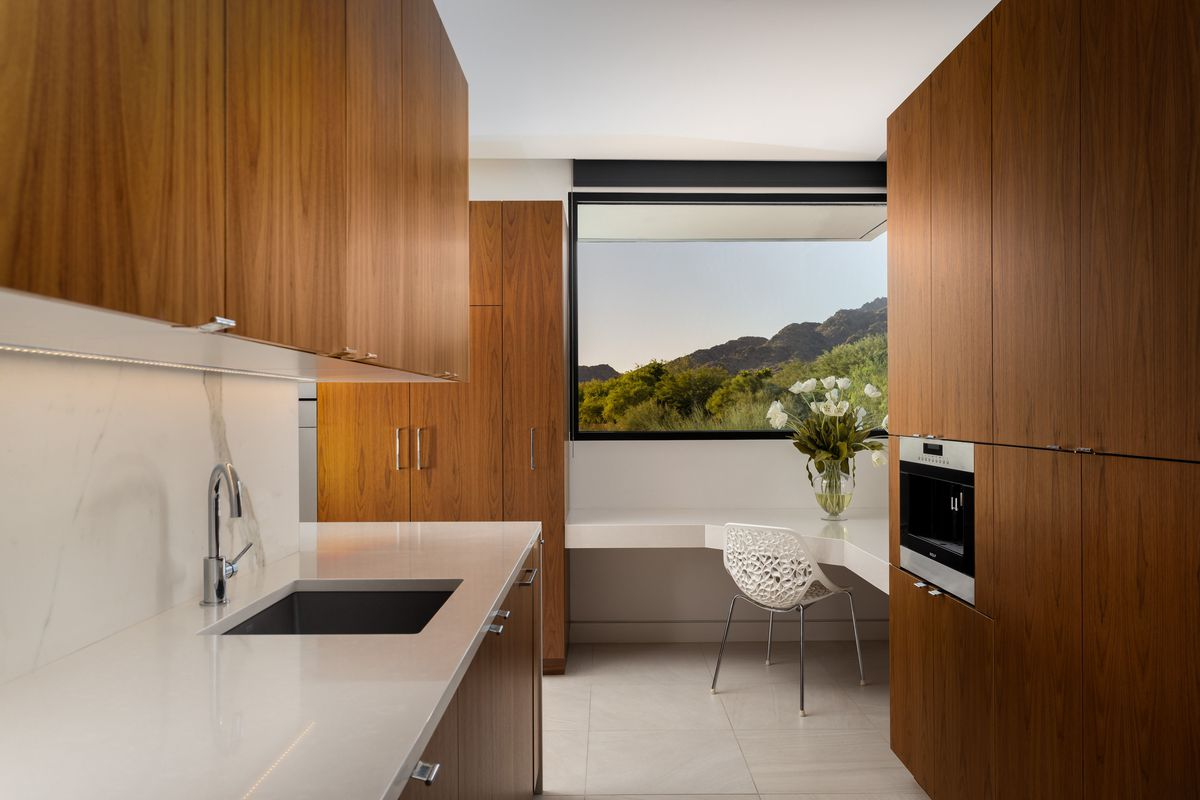 A corner of the kitchen with built-in white counters and a view of the desert landscape.