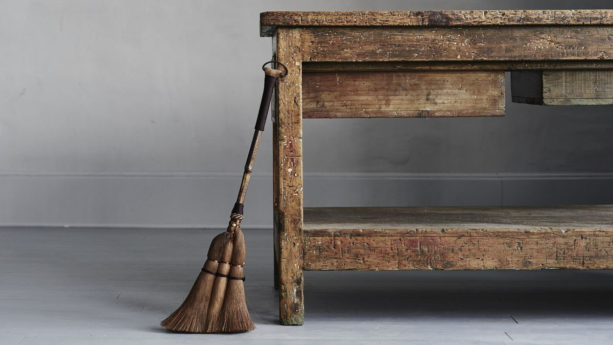 A broom leans against a wooden table.