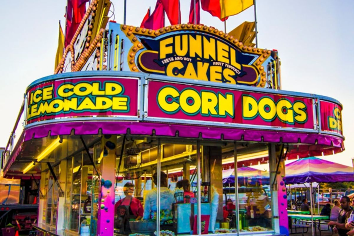 A brightly colored hot pink, yellow, and blue funnel cake and corn dog stall with flags flying above it at the state fair