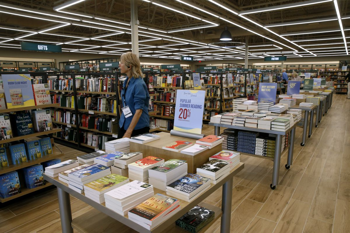 The interior of a bookstore with stacks of books on tables and on shelves.