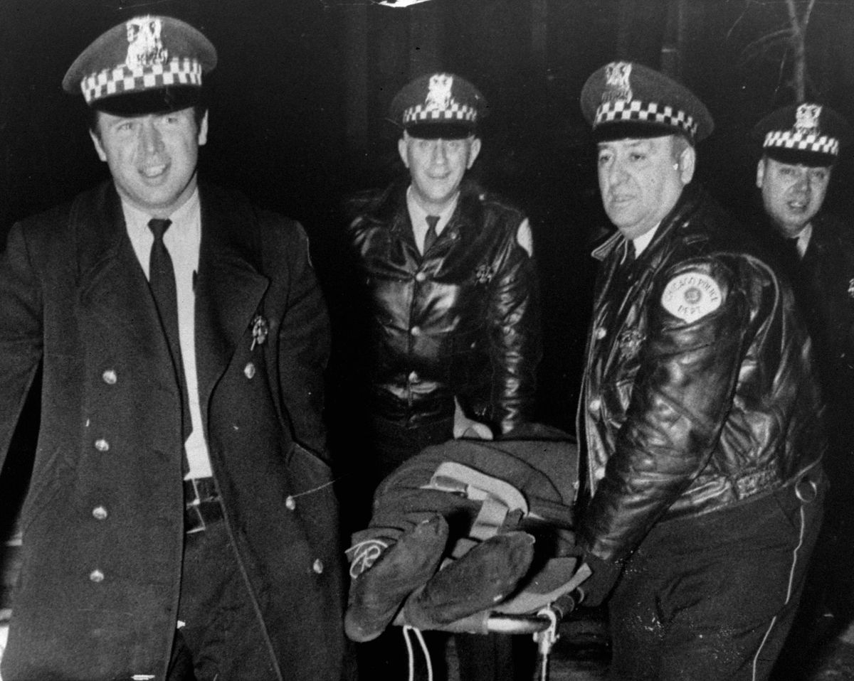 Chicago police officers move the body of Fred Hampton after he was shot and killed in 1969.