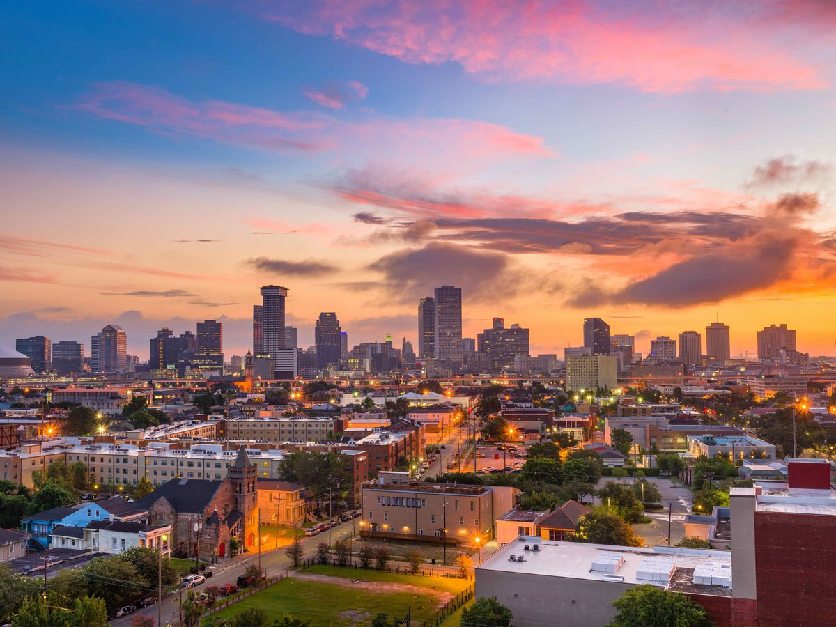 An aerial view of the cityscape of New Orleans. There are various buildings in the view. There is a sunset in the sky and the sky is pink, orange, blue, and purple.