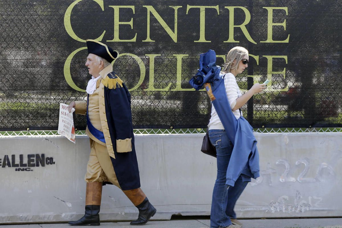 Paul Johnson, dressed as George Washington, left, walks past a barricade at Centre College, site of the vice presidential debate, Thursday, Oct. 11, 2012, in Danville, Ky. Vice President Joe Biden will face Republican vice presidential candidate, Rep. Pau