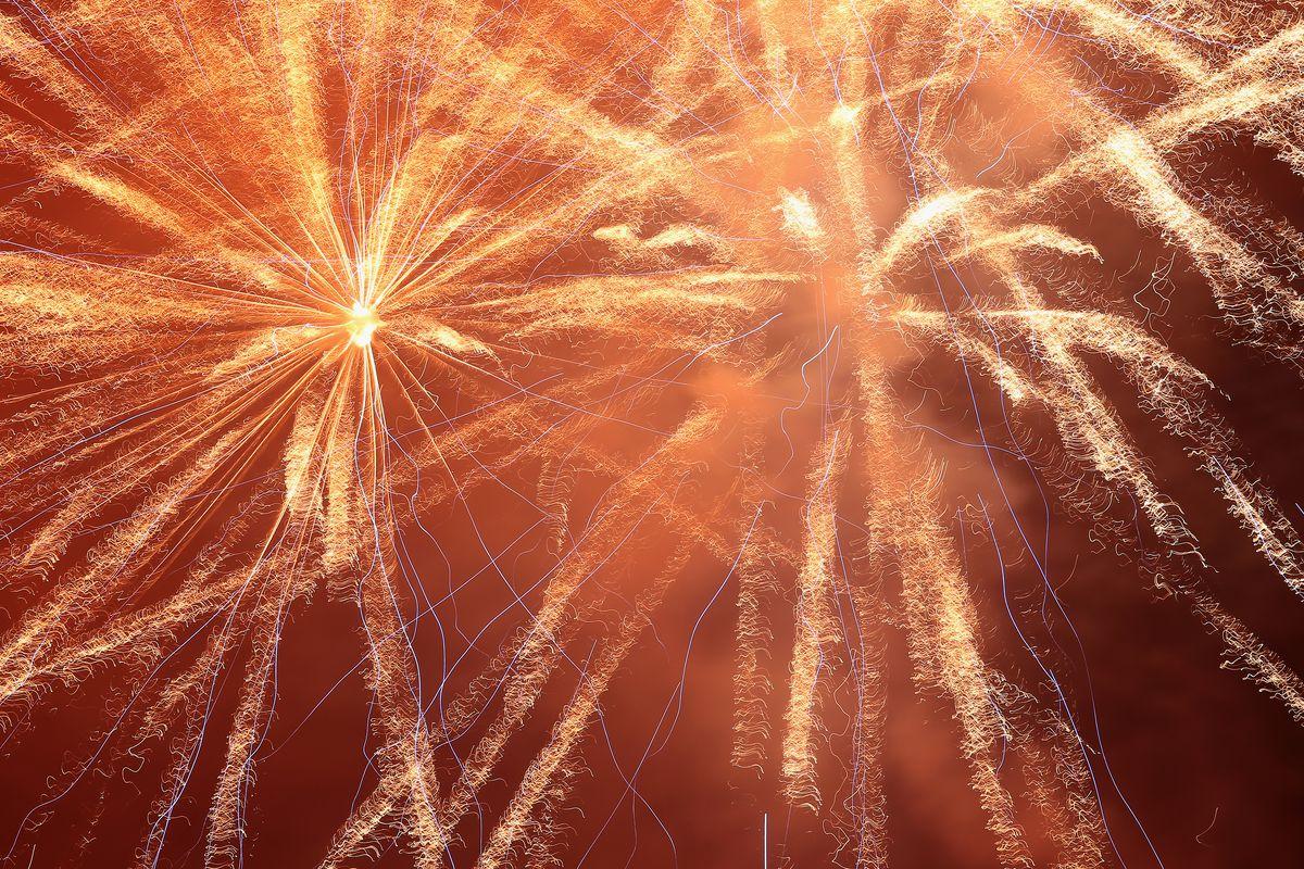 Golden starburst fireworks against an orange sky