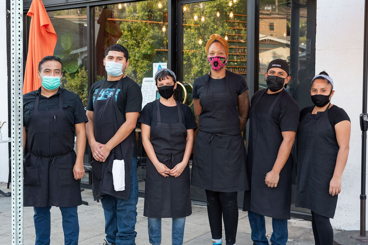 A group of staff members at a restaurant stand together while all wearing black and face masks.