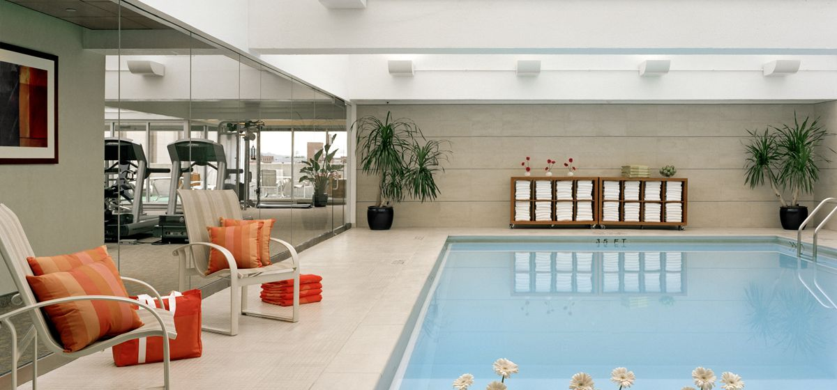 An indoor swimming pool. There is seating to the side of the pool.
