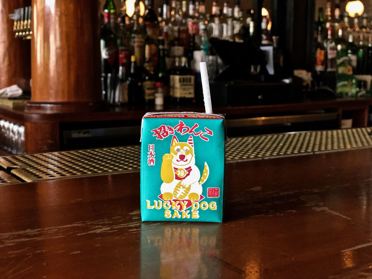 A small, square, turquoise juice box.