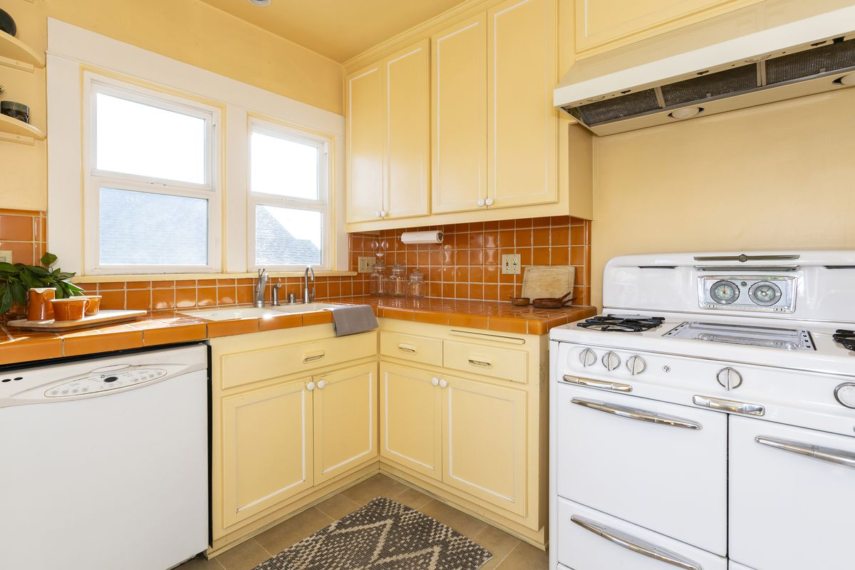 A yellow kitchen with orange counters and backsplash. A large vintage stove is also pictured.