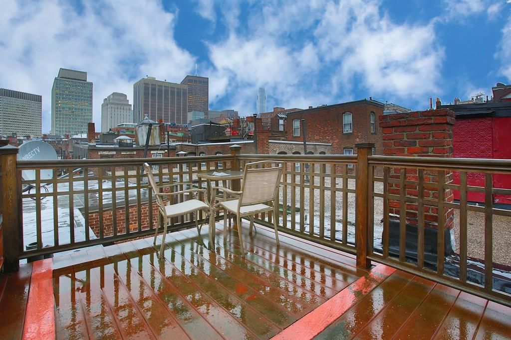 A rain-slicked roof deck looking out on a city skyline.