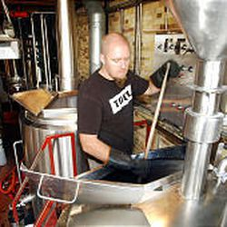 Jason Stock, assistant brewer at Squatters pub, mashes in grains during beer brewing process. Utah and three other states have a 3.2 percent alcohol limit for beer.
