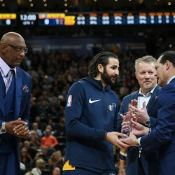 Utah Jazz guard Ricky Rubio, second from left, is presented with the NBA Cares Community Assist Award by NBA Cares ambassador Bob Lanier, NBA board of governors representative for the Utah Jazz's Greg Miller and physician Ronald Navarro, left to right, at Vivint Arena in Salt Lake City on Saturday, Dec. 30, 2017.