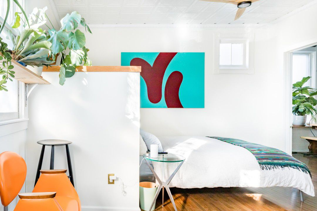 A bedroom with modern furniture, a colorful painting on the wall, and plants.