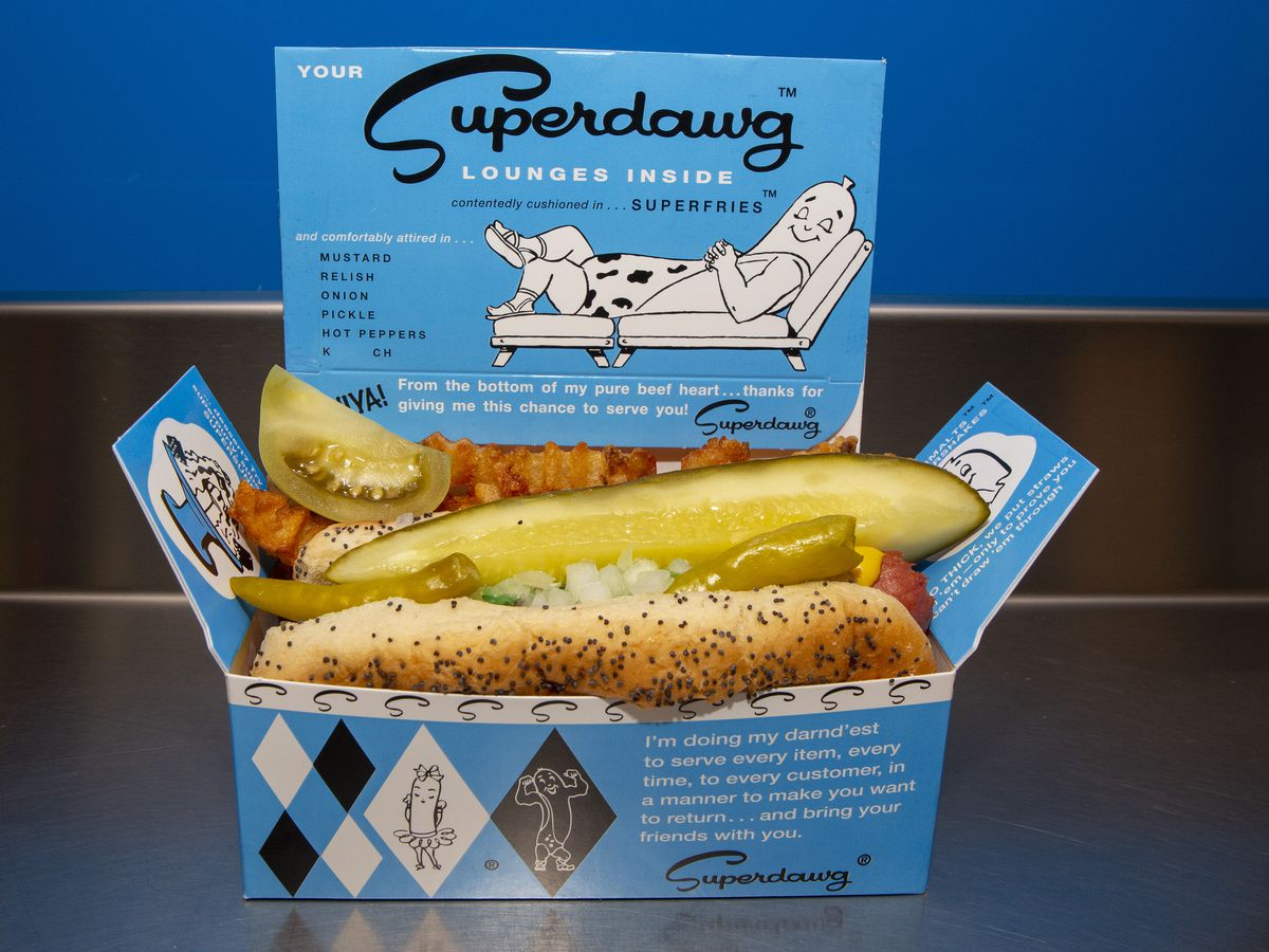 A blue cardboard rectangle food container with a hot dog inside.