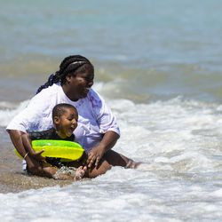 Precious Brown, 25, and her 3-year-old son Josiah Stingley, from the Roseland neighborhood, play in the waves of Lake Michigan at Rainbow Beach on the South Side, Wednesday afternoon, July 24, 2019.
