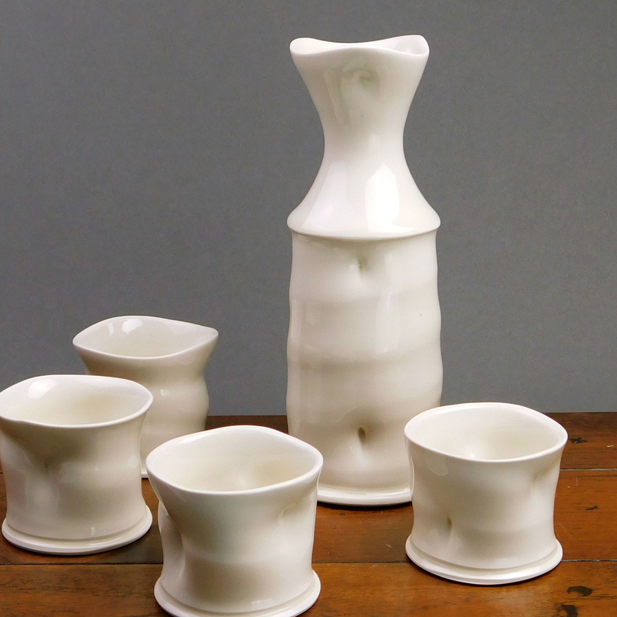 Multiple white porcelain carafes in assorted sizes sit on a wooden table.