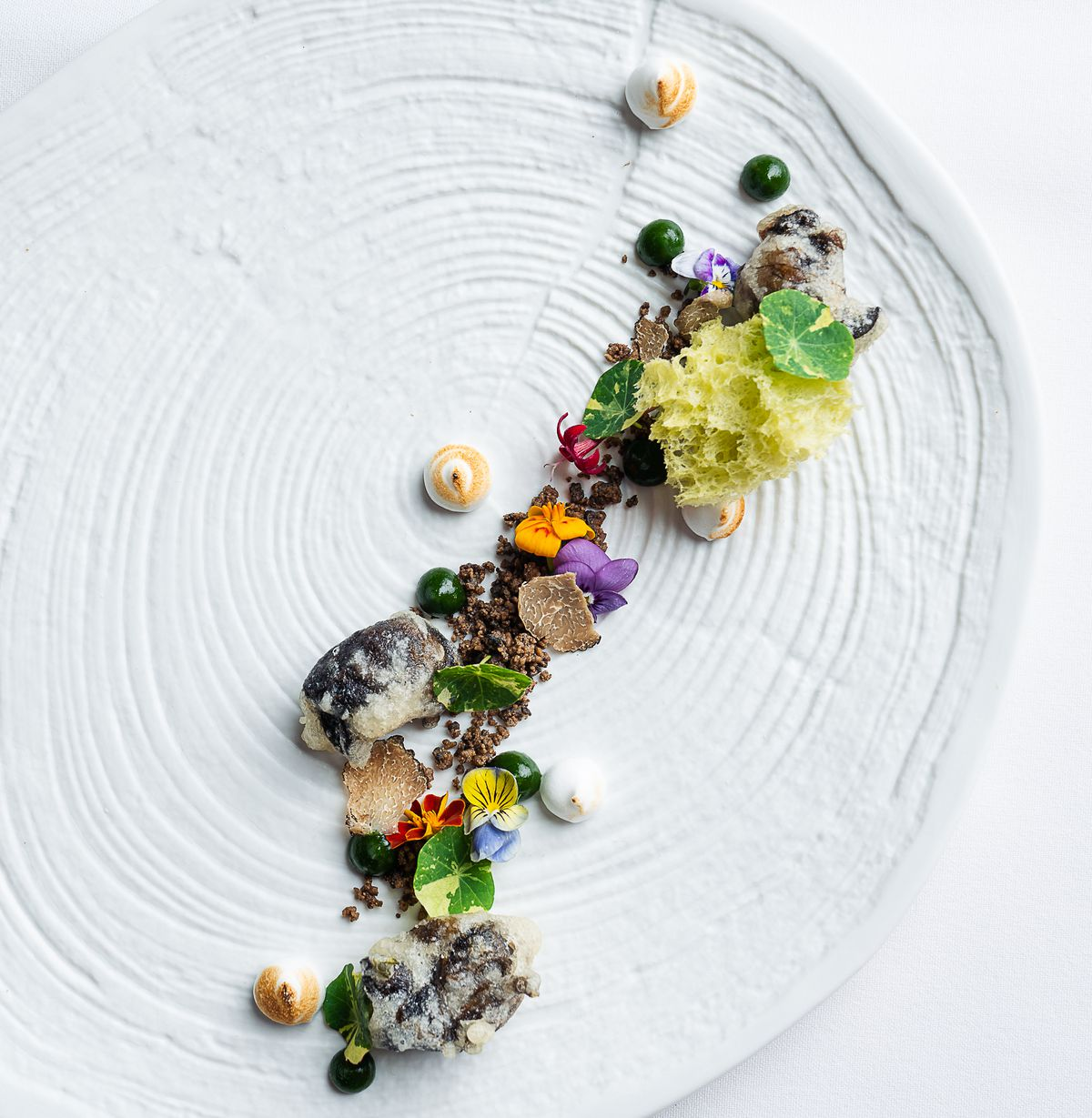 a dish with snails, flowers, and moss