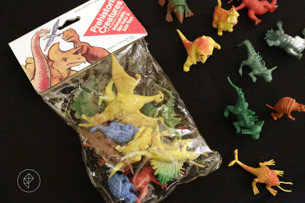 """A yellowing bag of plastic dinosaurs reads """"Prehistoric Creatures: 14 Realistic Creatures — Unbreakable, non-toxic, and safe-toys."""" The label shows they were made in Hong Kong. Toys similar to these were the inspiration for D&D's first monsters."""