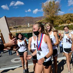 Morgan runners collect their trophy after taking the team title in the 3A girls state cross-country championships at Soldier Hollow in Midway on Thursday, Oct. 22, 2020.