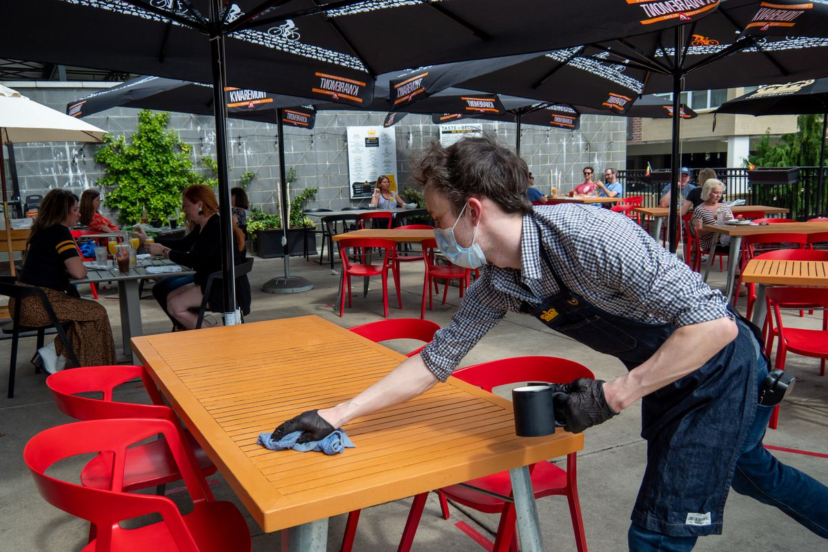 A worker in gloves and a mask wipes down an outdoor table with red chairs.