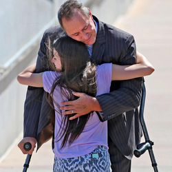 Former Utah Attorney General Mark Shurtleff is hugged by his daughter Annie as he leaves the Salt Lake County Jail after being booked and posting bond Tuesday, July 15, 2014, in South Salt Lake.