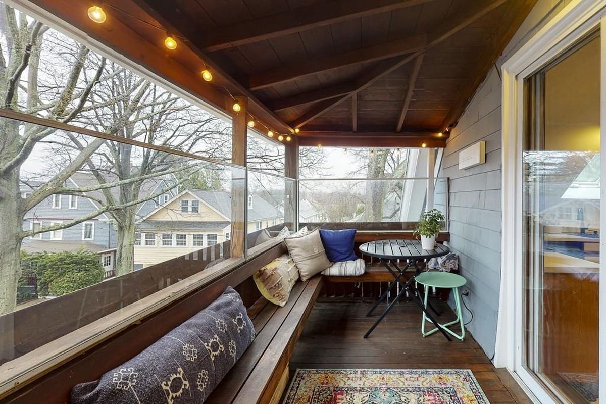 A long, narrow, enclosed deck with furniture.