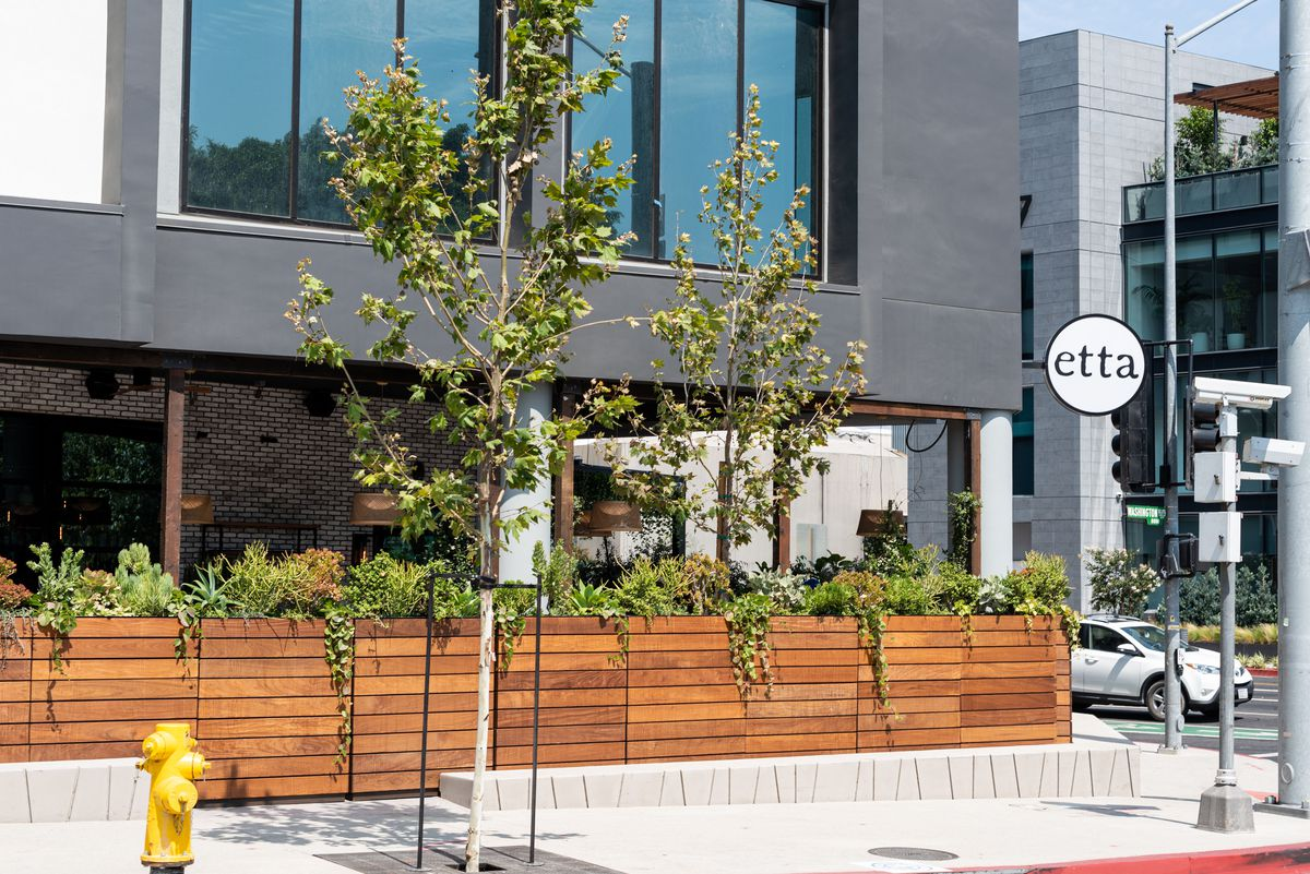 The sunny exterior of a restaurant with a patio, shown on the corner.