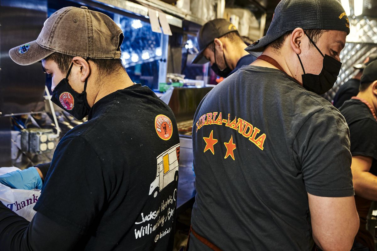 """Two employees wearing uniforms with the words """"Birria-Landia"""" stand in a small food truck kitchen"""