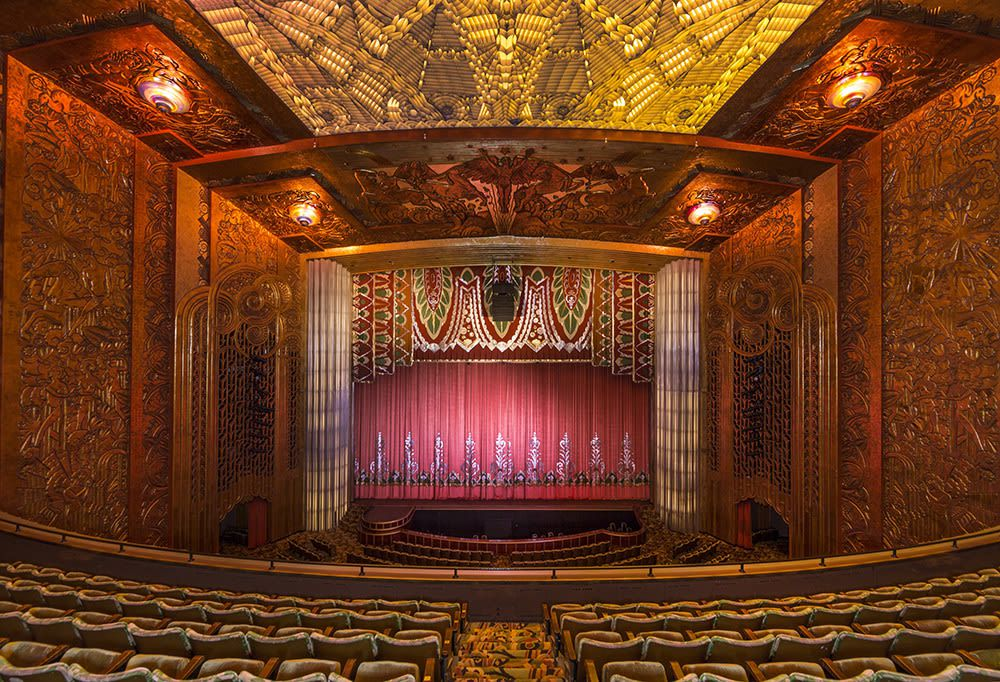 The interior of the Paramount Theatre in Oakland. The walls and ceiling are covered in elaborate metalwork. The stage has a red curtain which is flanked by a multicolored patterned curtain.