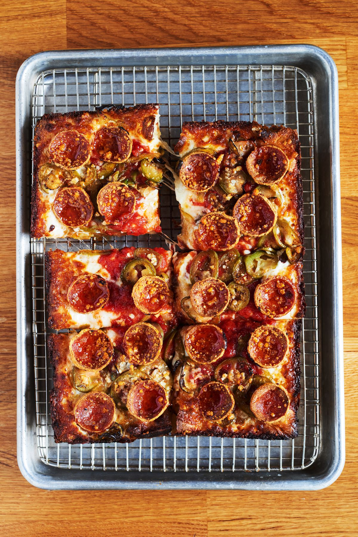 Six, thick square slices of the Colony2 pizza topped with pepperoni, pickled jalapeños, and drizzled in honey on a rectangular metal tray