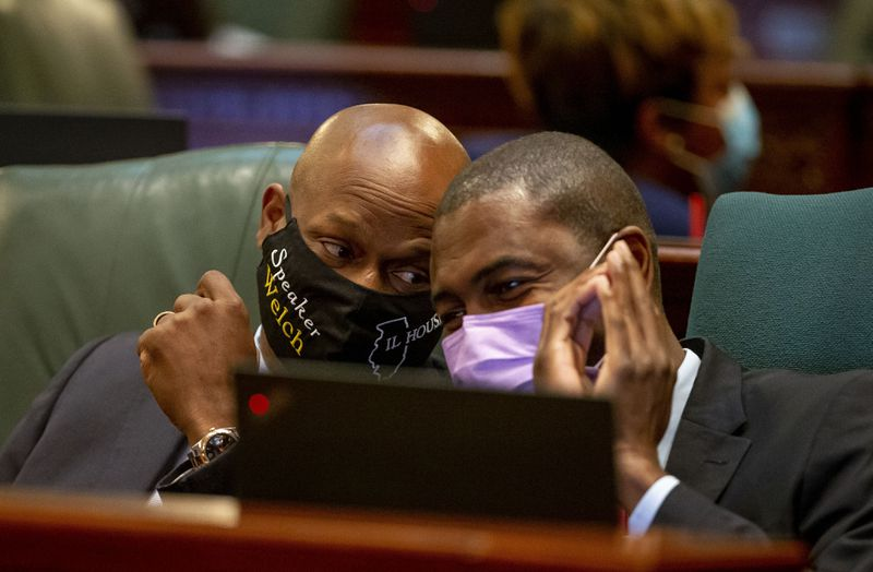"""House Speaker Emanuel """"Chris"""" Welch, D-Hillside, left, talks with state Rep. LaShawn Ford, D-Chicago, during debate of a comprehensive energy proposal, on the House floor on Thursday."""